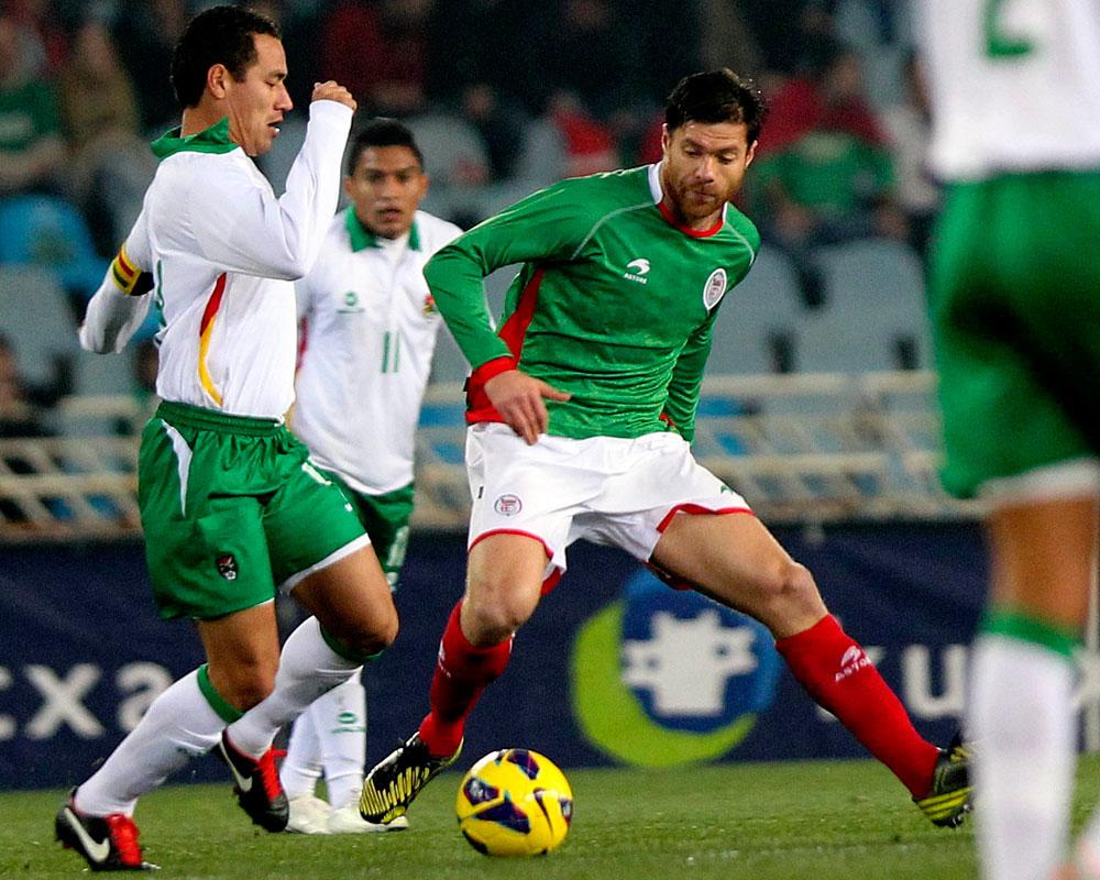 El jugador de la selección autonómica de Euskadi, Xabi Alonso (d) controla el balón ante Gualberto Mojica, de la selección de Bolivia. EFE