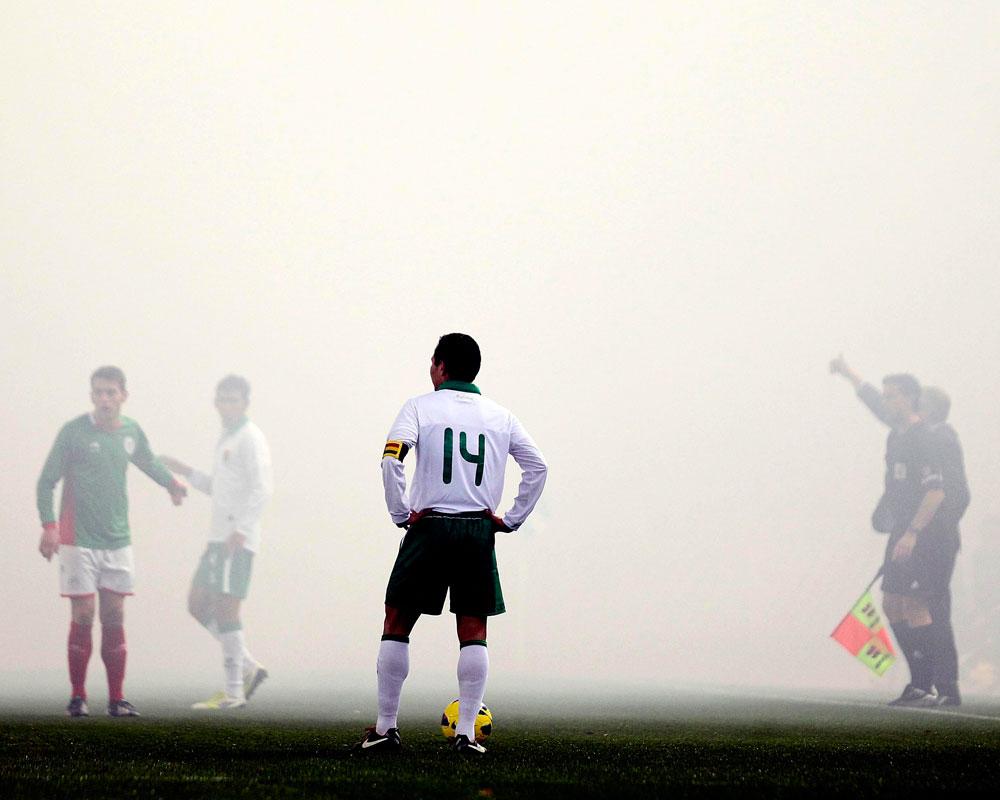 El capitán de la selección de Bolivia Gualberto Mojica espera a que se disipe el humo de bengalas, que durante algunos minutos detuvieron el partido. EFE