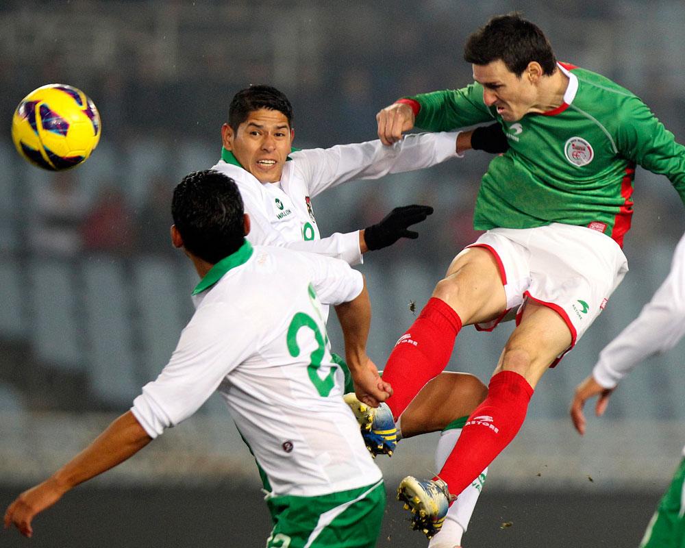 El jugador de la selección autonómica de Euskadi, Aduriz, remata un balón ante José Carlos Barba, de la selección de Bolivia. EFE