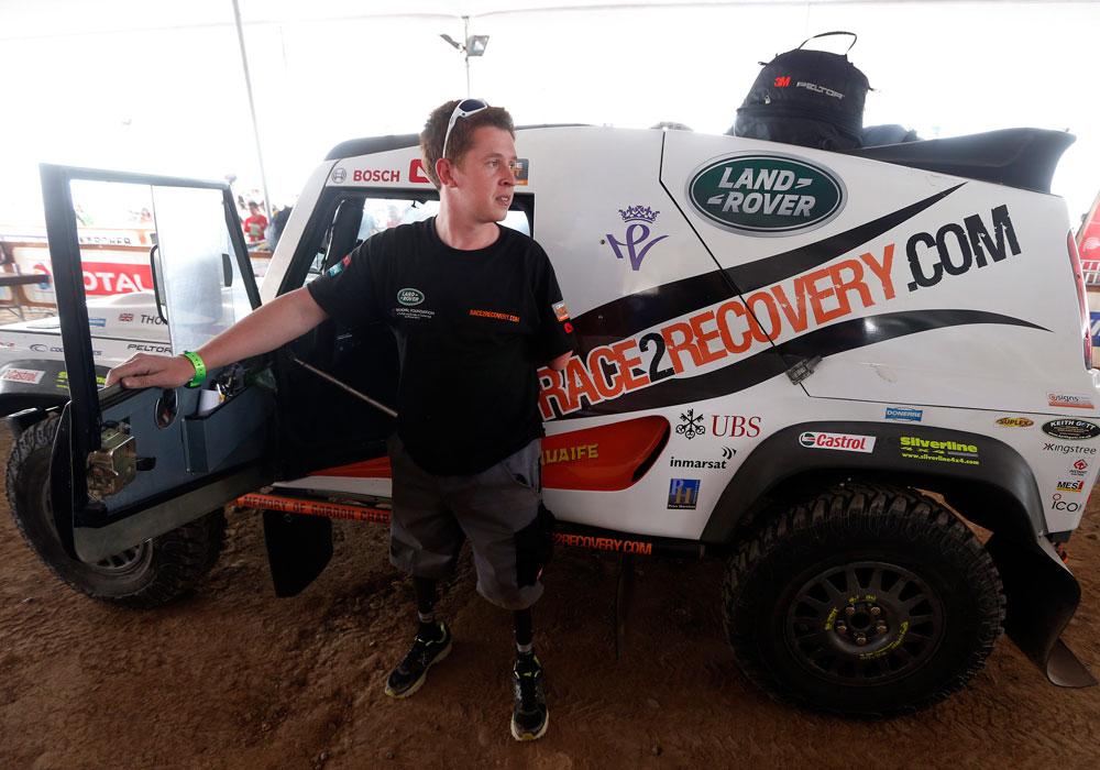 El copiloto británico Tom Neathway del equipo Race2Recovery junto a su coche durante el proceso de verificaciones técnicas. Foto: EFE