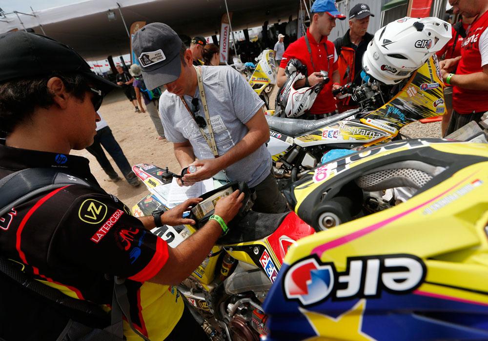El piloto chileno Jaime Prohens (i) pasa las verificaciones técnicas de su moto en el campamento del rally Dakar. Foto: EFE
