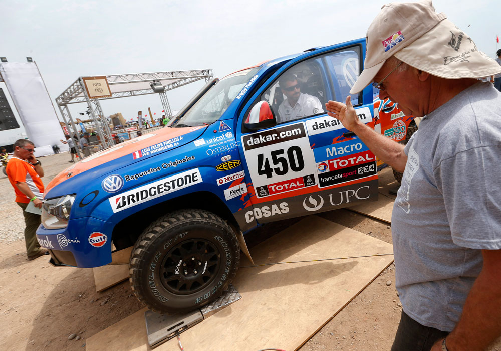 Un miembro de la organización da indicaciones a un vehículo durante el proceso de verificaciones técnicas en el campamento del rally Dakar. Foto: EFE