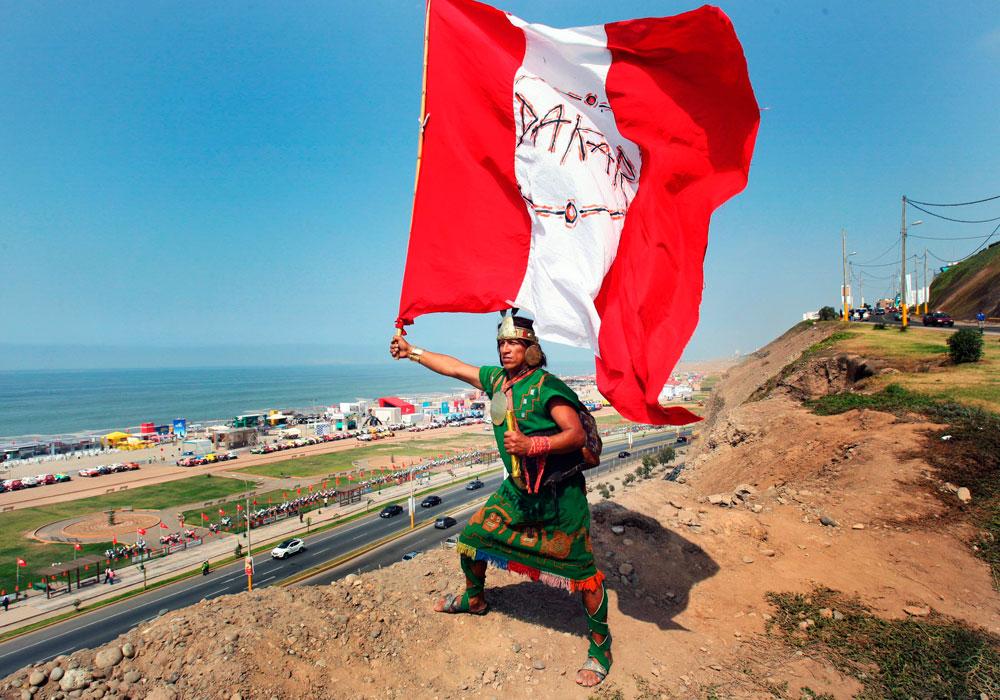 Un poblador de la limeña zona de Huaycán ondea una bandera de Perú anunciando la llegada del Dakar 2013. Foto: EFE