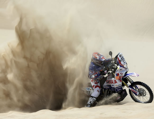 La piloto chilena Josefina Gardulski trata de sacar su moto varada en la arena en la segunda etapa del Rally Dakar en el desierto de Pisco (Perú). Foto: EFE