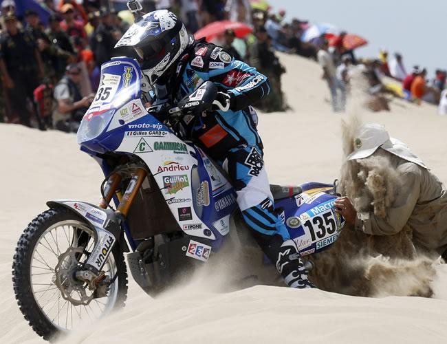 Un espectador trata de ayudar al piloto francés Gilles Gard varado en la arena en la segunda etapa del Rally Dakar en el desierto de Pisco (Perú). Foto: EFE