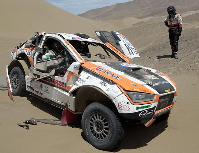 El piloto holandés Erik van Loon mira su coche tras volcar en una duna. EFE
