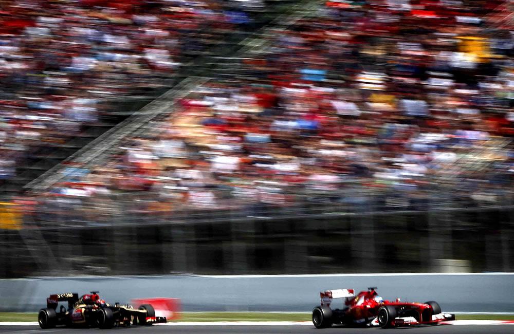 El piloto español de Ferrari, Fernando Alonso (d), conduce su monoplaza seguido por el finlandés de Lotus, Kimi Raikkonen, durante el Gran Premio de España. EFE