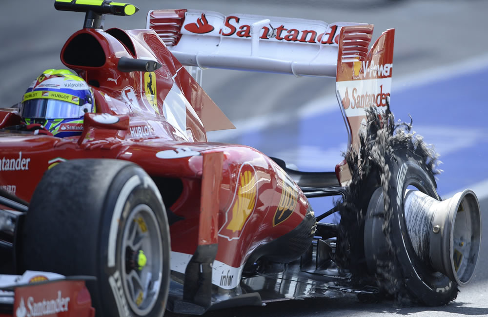 Felipe Massa de Ferrari ingresa a pits con su neumático dañado. EFE
