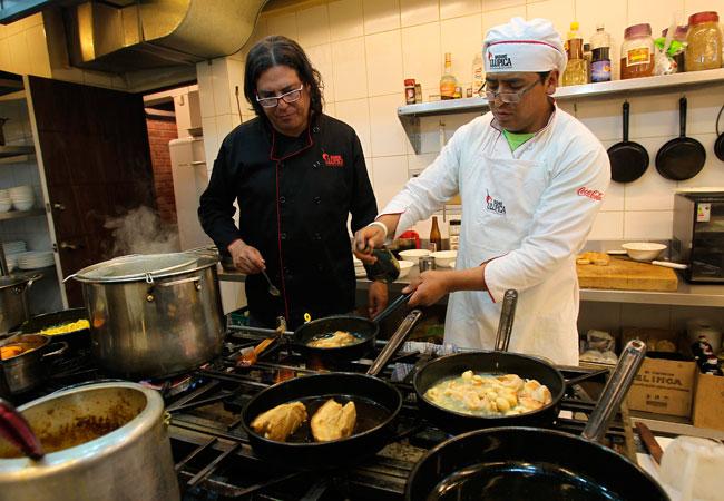 El chef del restaurante Madame Ulupica y uno de los socios de la empresa Made in Bolivia, Ilya Fortún (i), supervisa la preparación de los platos. EFE