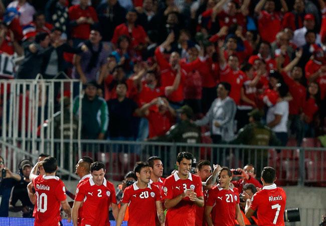 Los jugadores de la selección chilena de fútbol celebran junto a su público un gol contra Ecuador. EFE