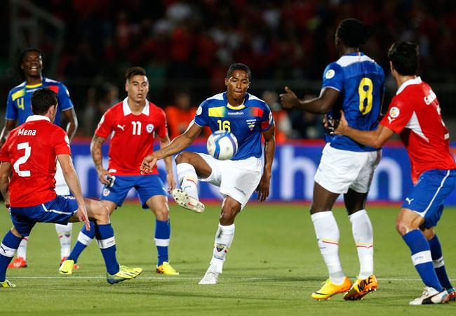 El jugador de la selección de Ecuador, Luis Antonio Valencia (c) trata de escapar a la marca chilena. EFE