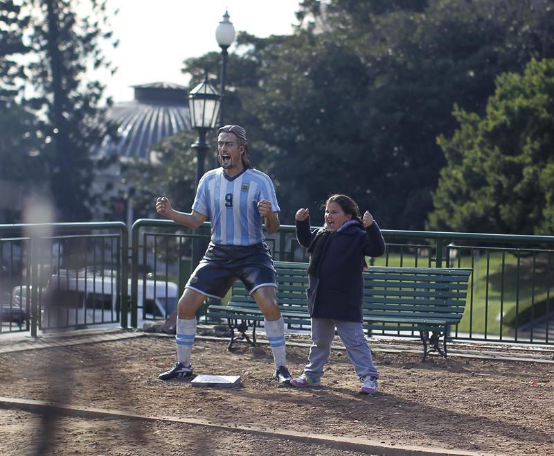 Una niña posa para una fotografía con la escultura del exjugador de la selección argentina Gabriel Batistuta. EFE