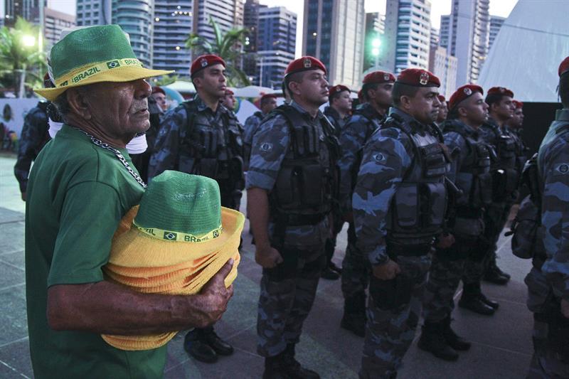 Un vendedor observa a personal de seguridad formando durante la inauguración de la FIFA Fan Fest. EFE