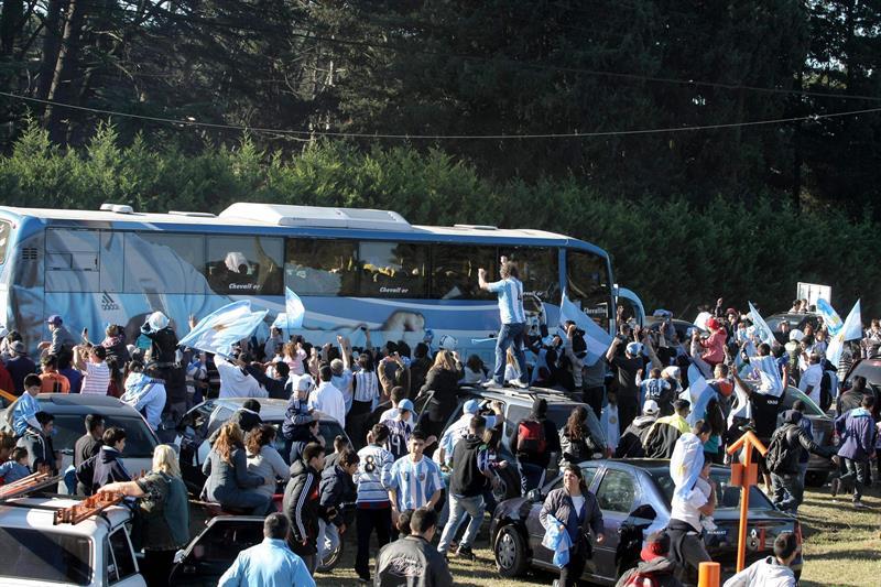 Hinchas saludan a los jugadores de la selección argentina camino al aeropuerto Ezeiza, donde tomarán un avión que los trasladará a Brasil. EFE