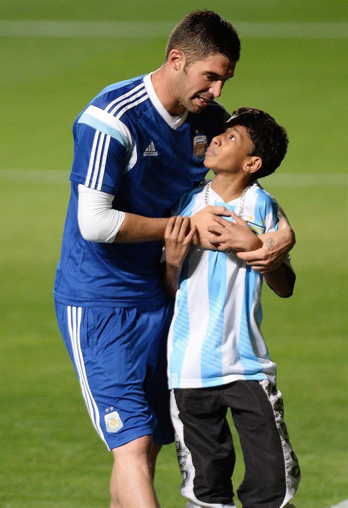 El jugador de Argentina Hugo Campagnaro abraza a un niño durante un entrenamiento. EFE