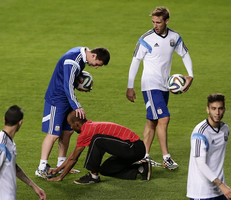 El jugador de Argentina Lionel Messi (i) toca la cabeza a un hincha mientras participa en un entrenamiento. EFE