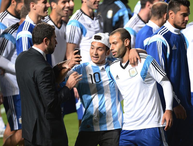 El jugador de Argentina Javier Mascherano (d) posa con un hincha que ingresó al campo durante un entrenamiento. EFE