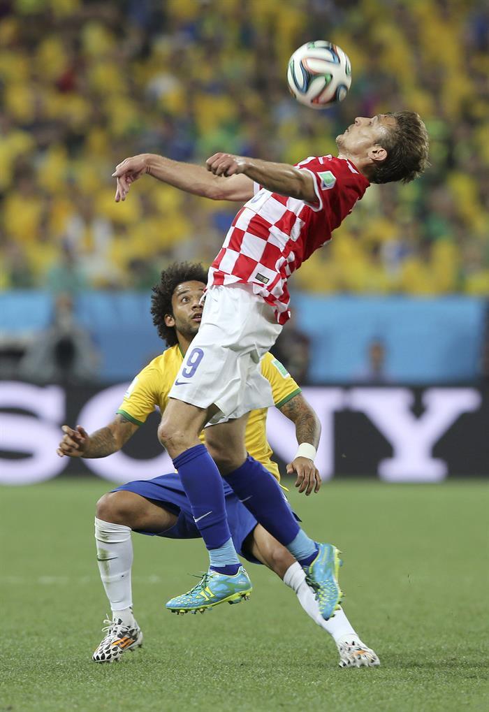 El delantero croata Nikica Jelavic controla el blaón ante el defensa brasileño Marcelo Vieira. EFE
