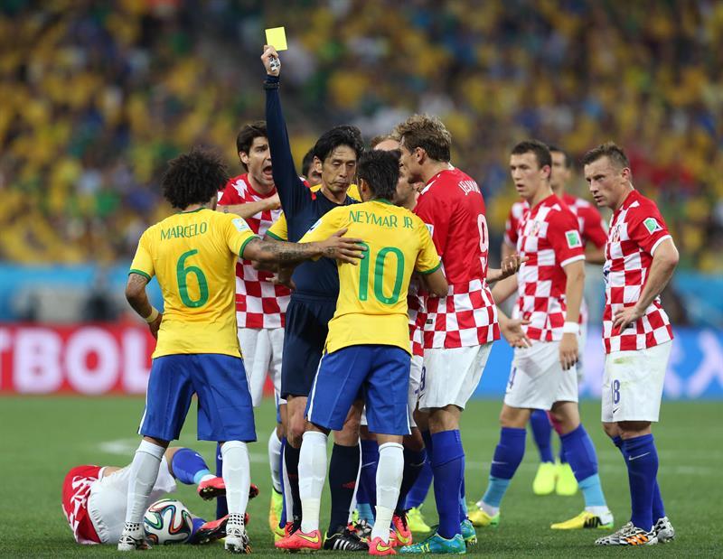 El árbitro japonés Yuichi Nishimura (2i) muestra tarjeta amarilla al delantero brasileño Neymar da Silva. EFE
