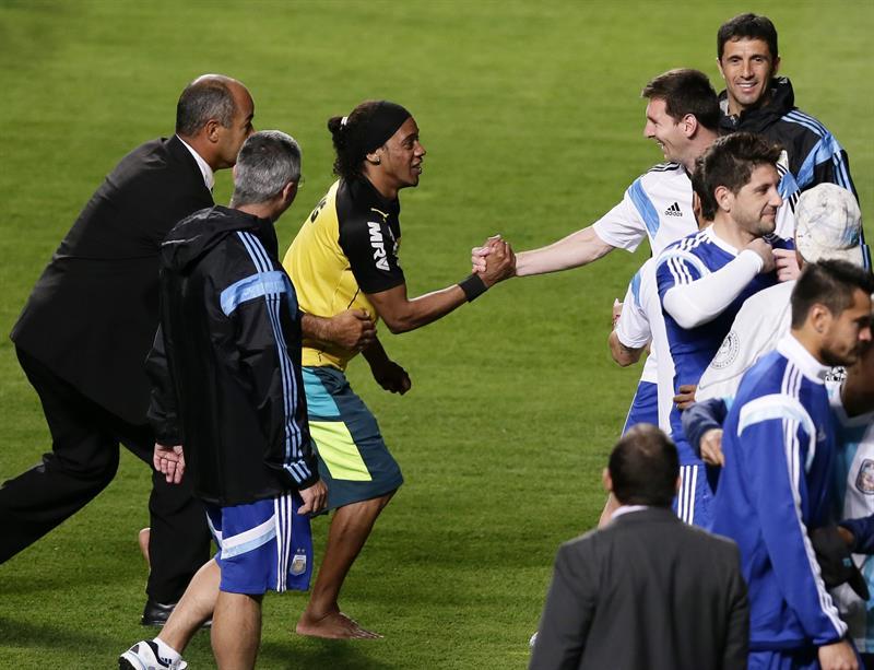 El jugador de Argentina Lionel Messi (d) saluda a un hincha parecido a Ronaldinho (c) que ingresó al campo. EFE