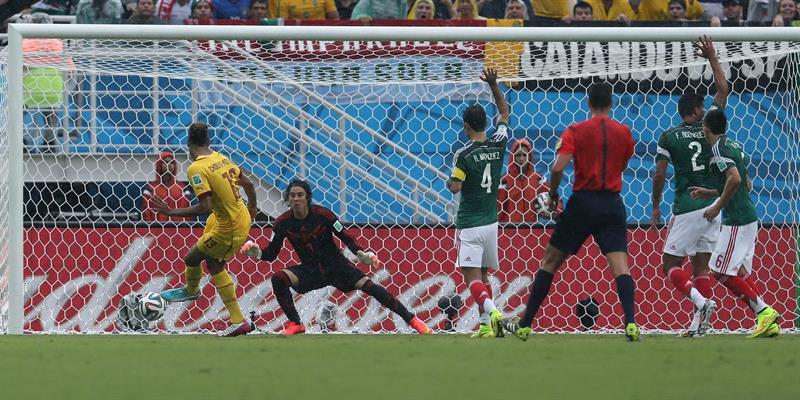 El delantero camerunés Eric Choupo Moting (i) dispara a puerta ante el guardameta Guillermo Ochoa (2i), mientras varios jugadores mexicanos reclaman . EFE