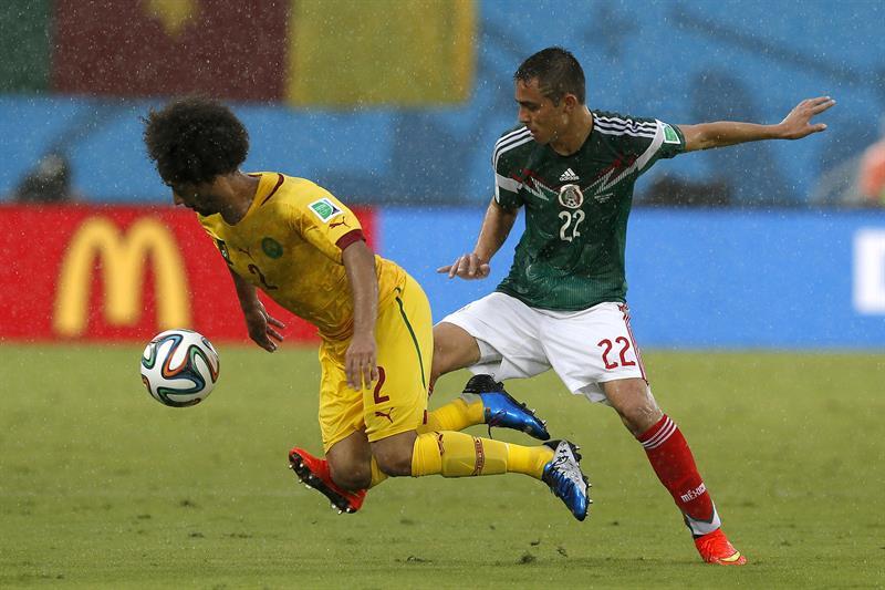El defensa camerunés Benoit Assou Ekotto (i) y el defensa mexicano Paul Aguilar luchan por el balón durante el partido México-Camerún. EFE