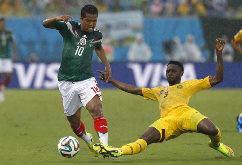 El delantero mexicano Giovani Dos Santos (i) y el defensa camerunés Nicolas Nkoulou luchan por el balón durante el partido México-Camerún. EFE