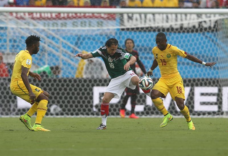 El defensa mexicano Andrés Guardado (c) lucha el balón con el centrocampista camerunés Eyong Enoh. EFE