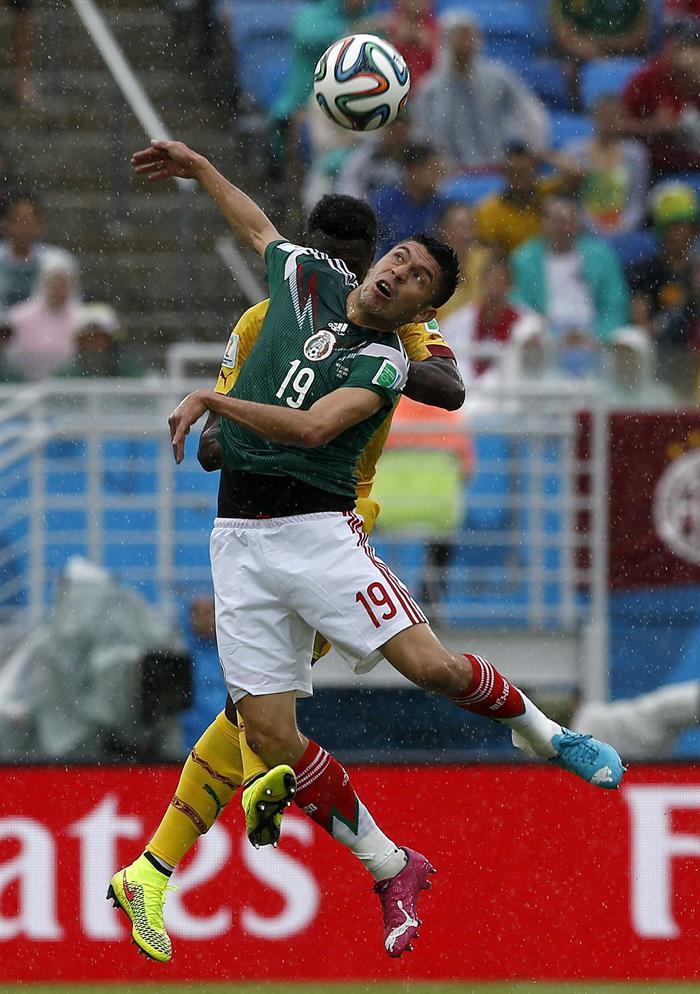 El delantero mexicano Oribe Peralta (en primer término) lucha un balón aéreo con el centrocampista camerunés Stephane Mbia (detrás). EFE