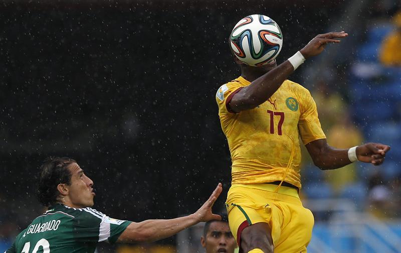 El centrocampista camerunés Stephane Mbia (d) controla el balón ante el defensa mexicano Andrés Guardado. EFE