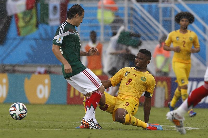 El centrocampista mexicano Andrés Guardado (i) lucha un balón con el delantero camerunés Samuel Etoo (d), durante el partido México - Camerún. EFE