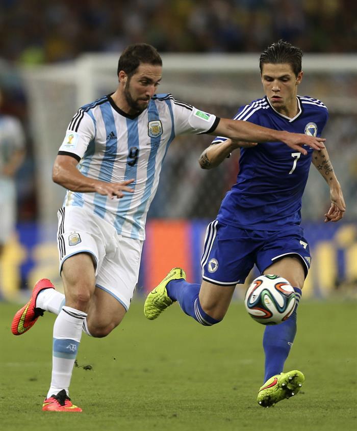 El delantero argentino Gonzalo Higuaín (i) lucha un balón con el centrocampista bosnio Muhamed Besic. EFE
