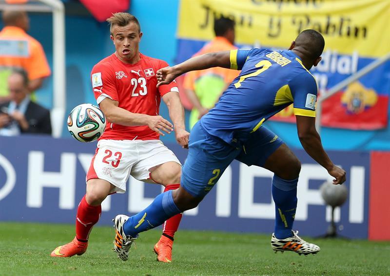 El defensa ecuatoriano Jorge Guagua (d) lucha un balón con el centrocampista suizo Xherdan Shaqiri,. EFE