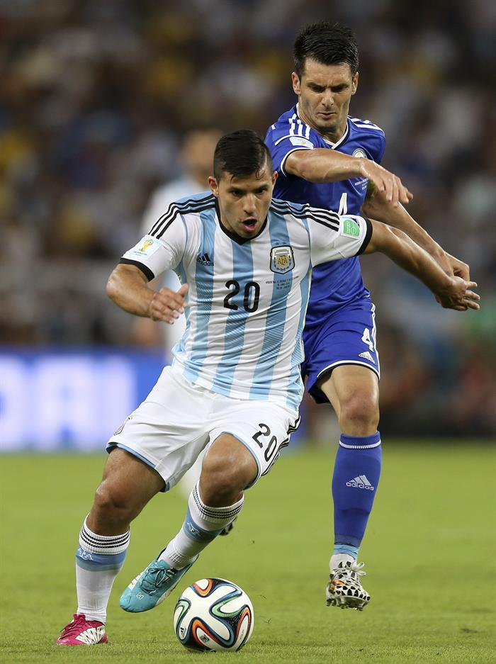 El delantero argentino Sergio 'Kun' Agüero controla el balón seguido por el defensa bosnio Emir Spahic, . EFE