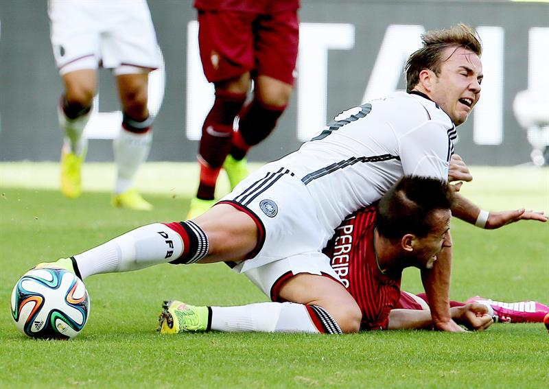 Joao Pereira of Portugal (R) fouls Mario Goetze of Germany (C) during the FIFA World Cup 2014. EFE