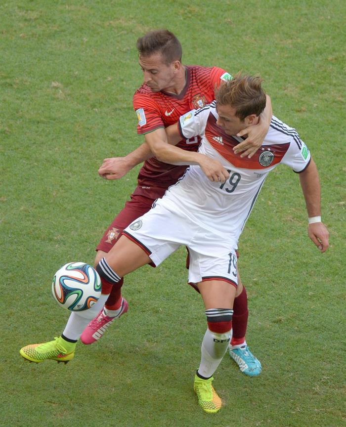 Portugal's Joao Pereira (C) tackles Germany's Mario Goetze (L) during the FIFA World Cup 2014 group G. EFE