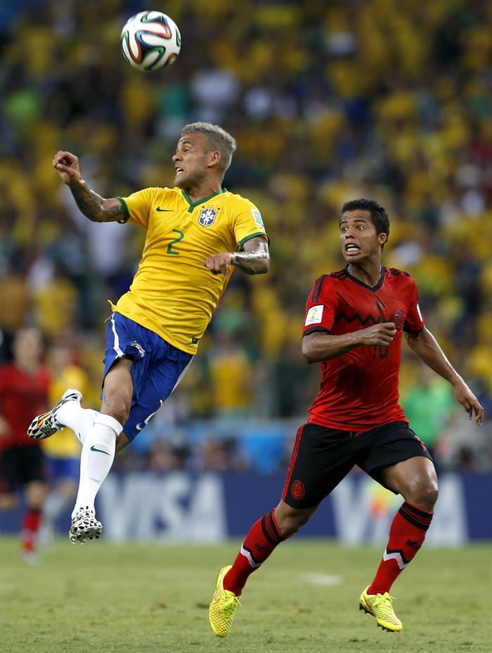 El defensa brasileño Dani Alves (i) despeja de cabeza ante el delantero mexicano Giovani Dos Santos. EFE