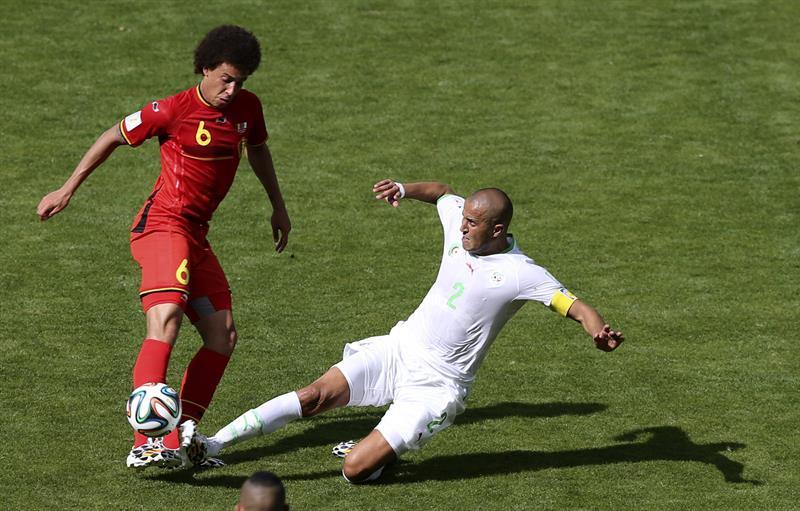 El defensa argelino Madjid Bouguerra (d) intenta arrebatar el balón al centrocampista belga Axel Witsel. Foto: EFE