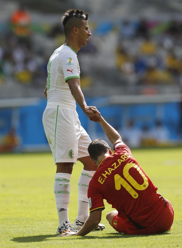 El centrocampista argelino Saphir Taider (i) ayuda a incorporarse al centrocampista belga Eden Hazard (d), durante el partido Bélgica-Argelia. Foto: EFE