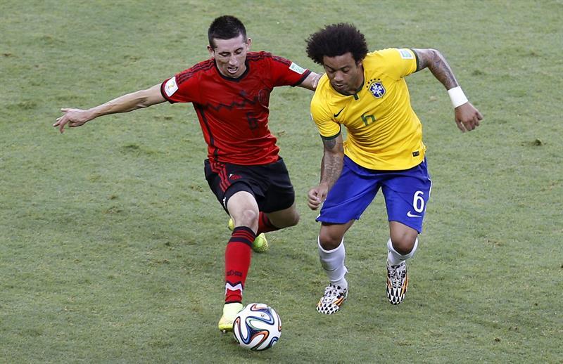 El defensa brasileño Marcelo Vieira (d) avanza con el balón ante el centrocampista mexicano Héctor Herrera. EFE