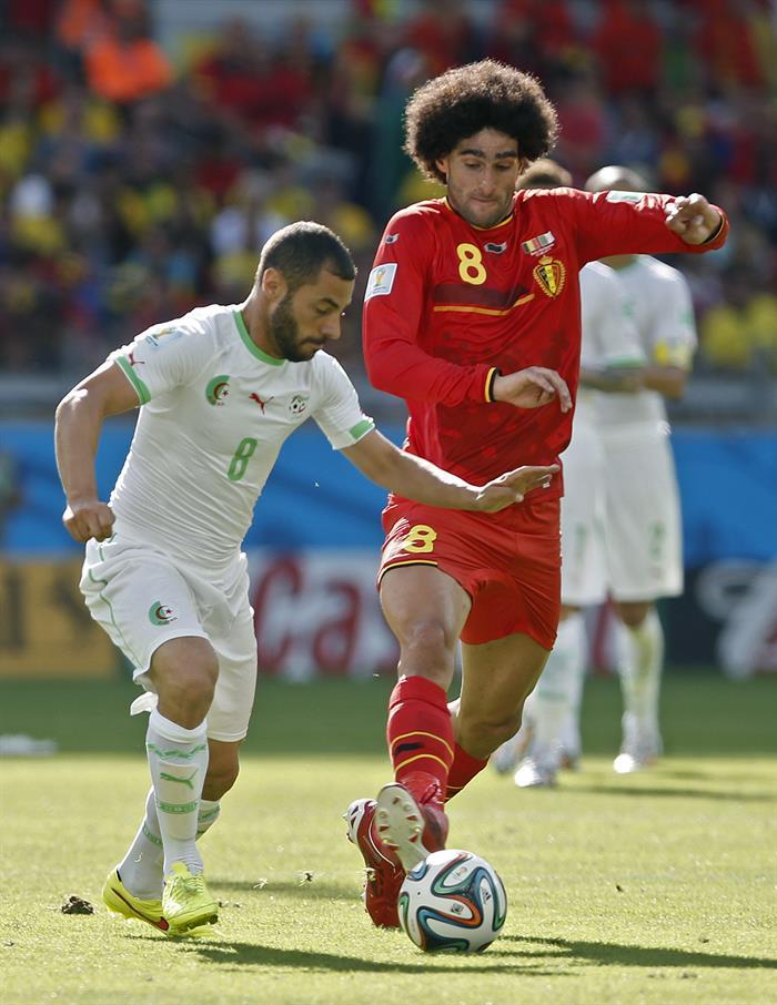 El centrocampista belga Marouane Fellaini (d) lucha un balón con el centrocampista argelino Mechi Lacen. Foto: EFE