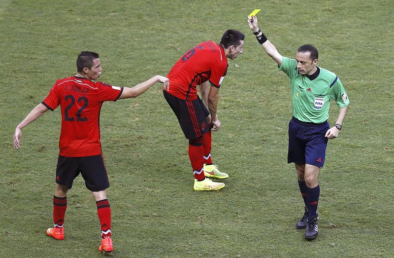 El árbitro turco Cuneyt Cakir (d) muestra tarjeta amarilla al defensa mexicano Paul Aguilar (i). EFE