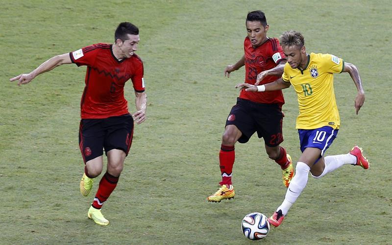 El delantero brasileño Neymar da Silva (d) controla el balón seguido por los jugadores de México. EFE