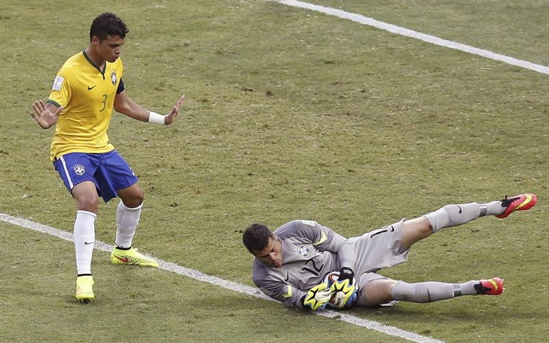 El guardameta brasileño Julio Cesar para el balón ante el defensa brasileño Thiago Silva. EFE
