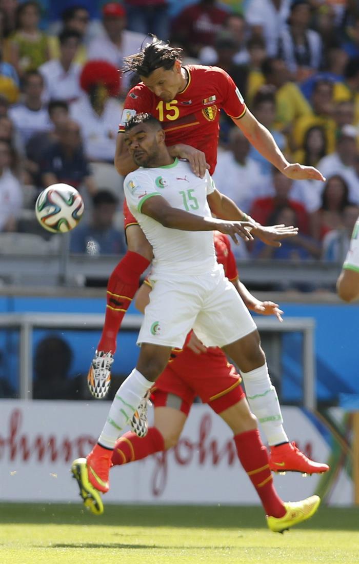 El defensa belga Daniel van Buyten (arriba) lucha un balón con el delantero argelino Abdelmoumene Djabou (abajo). Foto: EFE