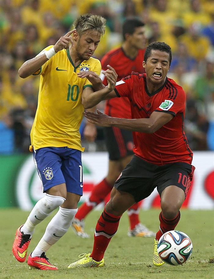 El delantero brasileño Neymar da Silva (i) lucha el balón con el delantero mexicano Giovani Dos Santos. EFE