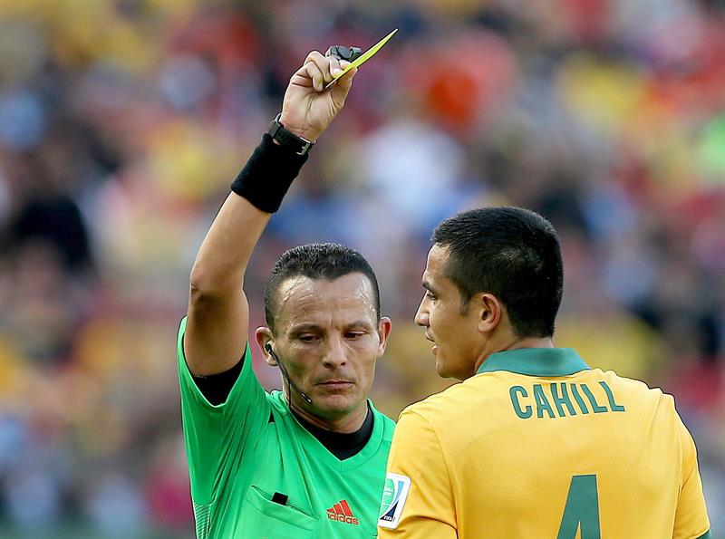 Referee Djamel Haimoudi of Algeria shows the yellow card to Australia's Tim Cahill during the FIFA World Cup 2014 group B. EFE