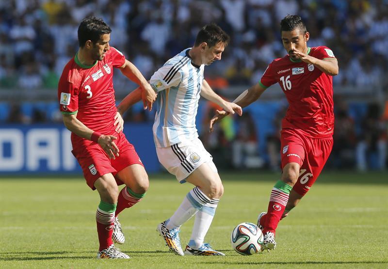 El delantero argentino Lionel Messi (c) controla el balón ante los jugadores de Irán, Ehsan Haji Safi (i). EFE