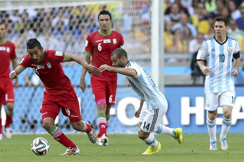 El delantero iraní Reza Ghoochannejad (i) ante el centrocampista argentino Javier Mascherano. EFE