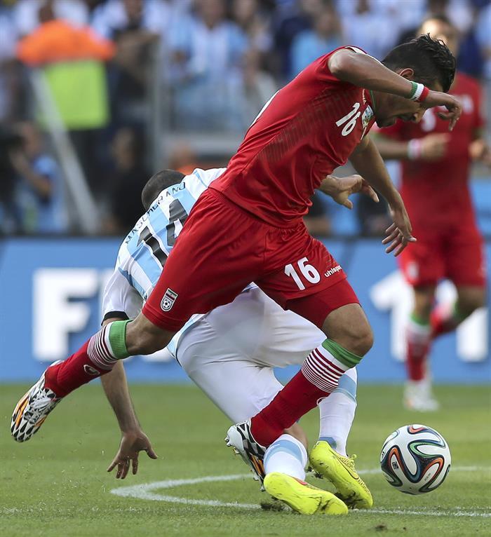 El delantero iraní Reza Ghoochannejad (d) lucha un balón con el centrocampista argentino Javier Mascherano (detrás). EFE